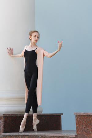 A young slender ballerina dances by the building. Beauty and grace movements. She stands on tiptoe.