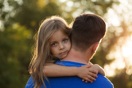 Family time. The father holds the daughter in his arms. The little girl hugs him tightly around his neck. Stock Photo
