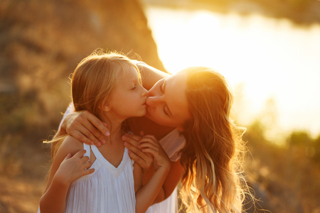 Family, mother and daughter on the river bank. A girl is kissing her daughter. Girls in white dresses. They are blondes. Family time together.