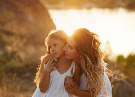 Family, mother and daughter at sunset. The girl bends down and looks at the distance with her daughter. Girls in white dresses. They are blondes. Family time together.