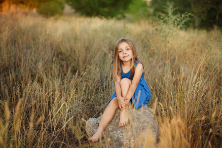A little girl in a blue dress is sitting on the stones in the middle of the meadow. She's barefoot