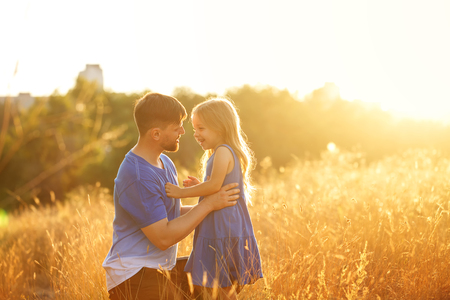Family time. Father and daughter on the meadow at sunset. They talk and look into each others eyes. Leisure together.
