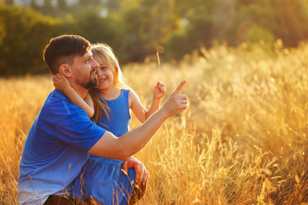 Family time. Father and daughter in the meadow. They embrace and look at the setting sun. He shows up. Leisure together. Stock fotó