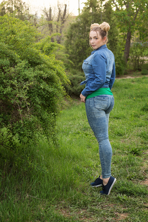 Young attractive girl is walking in the spring park. She is dressed in a denim shirt and tight jeans