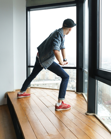 Teenage boy in denim jacket and baseball cap, jeans and sneakers dances by window in dance studio. Hip-hop movement. Dynamics of modern dance