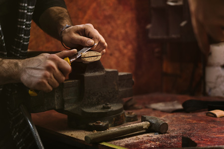 Man works in carpentry workshop. He cuts off excess wood with knife with an ax. Banco de Imagens