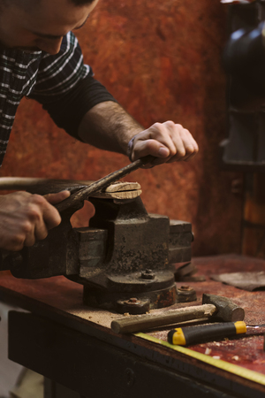 Man works in carpentry workshop. He files excess wood with an ax.