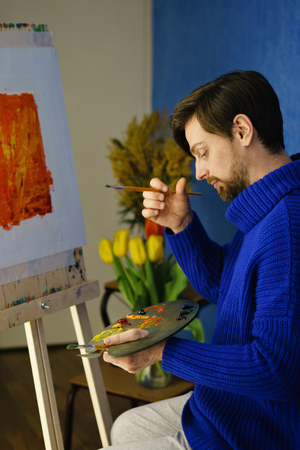 Artist in blue sweater pondered. He holds palette, bristle brush. Man is sitting in front of easel. Flowers in the background Фото со стока