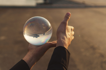 Contact juggling. Hands and glass ball. Inverted panorama of the city in the reflection of the ball. Mastery of representation. Close-up photo at sunset. Stok Fotoğraf