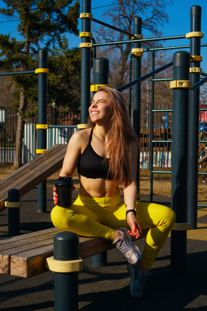 Girl on street workout. She rests on board and drinks water from bottle after strength exercises. Girl is dressed in black topic and yellow pants. She smiles at spring sun