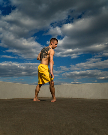 Tricking on street. Martial arts. Man stands in rack for roundhouse kick barefoot. Shooted from bottom foreshortening against sky.