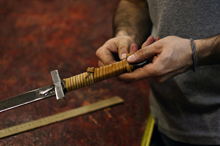 Smith makes leather winding of sword. Man is working in workshop. He fixes leather band on hilt of sword.