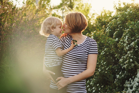 Mother and son in striped T-shirts. Woman holds boy in her arms and kisses him in nose. Family time