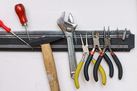 Set of tanner tools close-up. An awl, screwdriver, hammer, wrench, pliers and wire cutters hang on magnetic holder. Banco de Imagens
