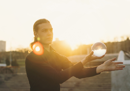 Contact juggling. Man balancing a glass bowl on hand. Glare of setting sun in frame. Skill performance. Trending view