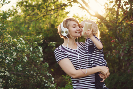 Mother and son in striped T-shirts. Woman listens to music on headphones and holds boy in her arms. He holds cell phone and kisses his mother. Family time together. Stock Photo