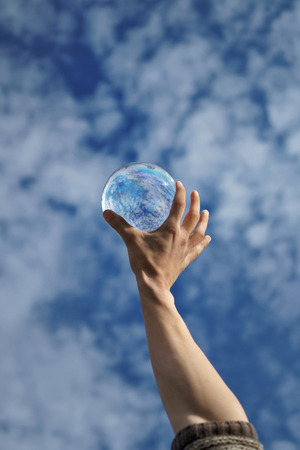Contact juggling. Hand and acrylic ball against sky. Cumulus clouds are reflected in sphere