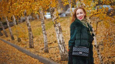 Red-haired girl in autumn park. She in short coat and gloves holds bag in her hands. Portrait on background of birches with yellow leaves.