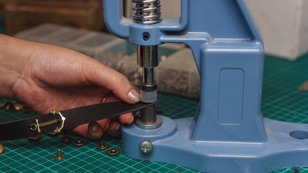 Tanner puts rivets on leather bracelet. Close-up photo. Process of working in workshop.