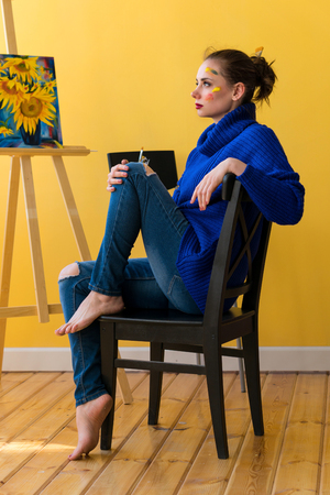 Girl artist sitting on chair in sweater and jeans. She is barefoot and with dirty face in paint. In background picture with sunflowers on easel.