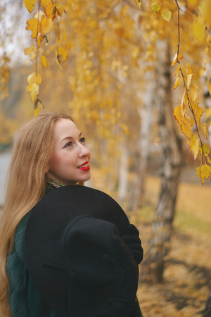 Red-haired girl in autumn park. She in short coat and gloves holds hat with wide margins in her hands. Female lips in red lipstick.