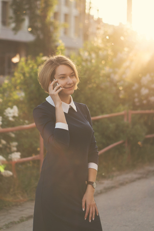 Attractive girl on city street at sunset. She is talking on her cell phone. Business lady is always in touch.