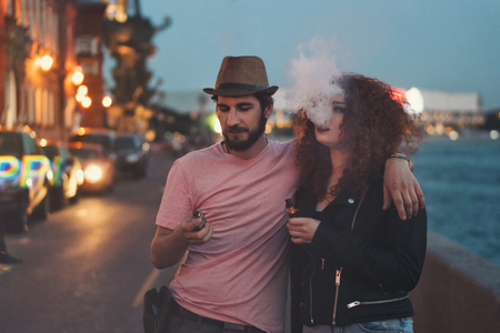 Loving couple of hipsters on date. Guy in hat and T-shirt is holding electronic cigarette and hugging girlfriend. Girl with curly red hair smokes an ecigarette. They are in streets of evening city. Stockfoto - 104039392