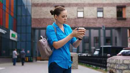 Young attractive girl with backpack holding cup of coffee. She stands on street of city.