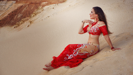 Oriental Beauty dancing sensual belly dance outdoors. Arab dance of seduction. Girl sat down on the sand dune.