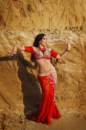 Oriental Beauty dancing sensual belly dance outdoors. Arab dance of seduction. Girl in red dress moves gracefully in dance. Archivio Fotografico