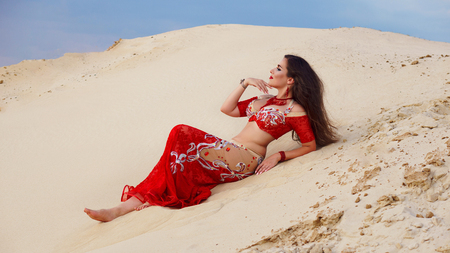 Oriental Beauty dancing sensual belly dance outdoors. Arab dance of seduction. Girl lies on sand dunes.