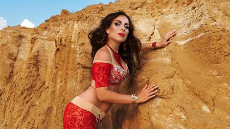 Belleza oriental bailando danza del vientre sensual al aire libre. Danza árabe de seducción. Chica con un vestido rojo.