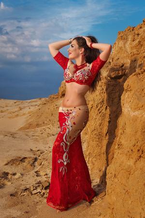 Belleza oriental bailando danza del vientre sensual al aire libre. Danza árabe de seducción. Una chica con un vestido rojo se alisa el cabello.