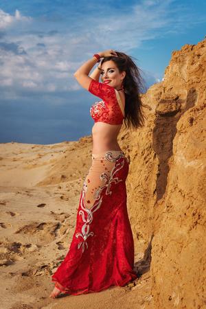 Orientalische Schönheit tanzt sinnlichen Bauchtanz im Freien. Arabischer Tanz der Verführung. Ein Mädchen in einem roten Kleid glättet ihre Haare. Porträt in voller Länge