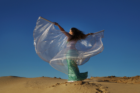 Oriental Beauty dancing belly dance with wings. Middle Eastern art. The girl in the desert. She waves her wings and moves along sand dunes. Woman is unrecognizable