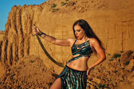 Oriental Beauty dancing belly dance with a sword in the desert. Dangerous houri and heavenly pleasures. Portrait on a background of sand dunes