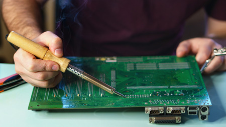 Repair motherboard. A man soldering solder the contacts from the motherboard. Craft fix. Close-ups