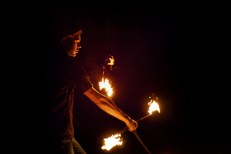 Fire show. Fakir dances with two Staff. Night performance. Fire and smoke. Fascinating flame movement. Submission elements of fire.