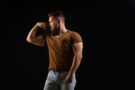 Bodybuilder portrait. Muscular man with a beard in a tight t-shirt showing biceps. Stylish and sporty young man.