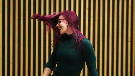 Cute young girl dancing on background of simple geometric pattern. Girl has eggplant hair flying in motion. She is in dark green dress. Pleasure and ecstasy of dance