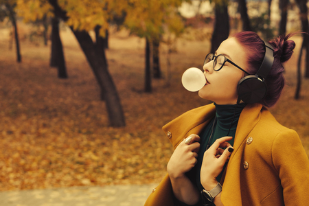 Cute young girl listening to music on headphones in autumn park. The girl has eggplant hair. She is wearing glasses and a mustard-colored coat. Woman bubbled up bubble gum 版權商用圖片