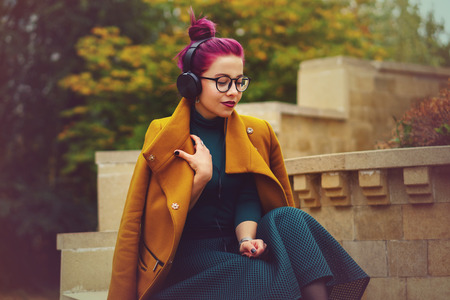 Cute young girl listening to music on headphones in autumn park. Girl has eggplant hair. Woman enjoys melody. She is wearing glasses and mustard-colored coat.