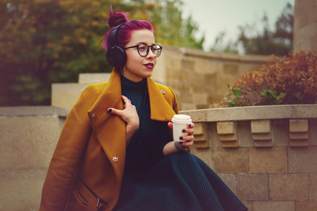 Cute young girl listening to music on headphones in autumn park. Woman is holding paper cup with hot drink. Girl has eggplant hair. She is wearing glasses and mustard-colored coat.