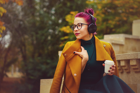 Cute young girl listening to music on headphones in autumn park. Woman is holding paper cup with hot coffee. Girl has eggplant hair. She is wearing glasses and mustard-colored coat.