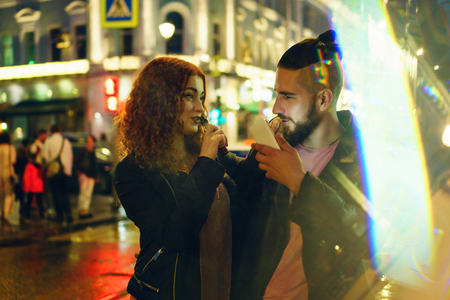 Couple in love on date. Boyfriend holding phone. She hugs him and smokes an electronic cigarette. They look at each other in street of night city. Wet asphalt after rain.