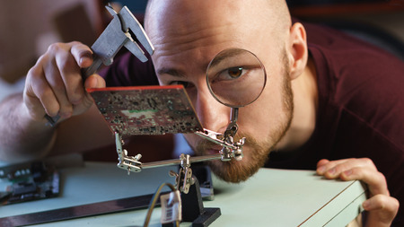 Repair motherboard. Service technician looks through magnifying glass. Chip is on latches. Troubleshooting.