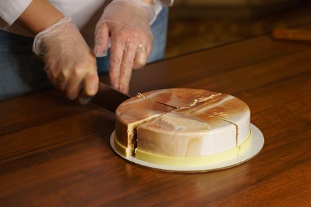 Esterhazy mousse cake. Woman cuts off a piece of cake. Mirror glaze glitters deliciously. Modern cooking. Cooking in a pastry shop.