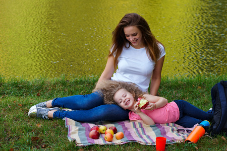 Family picnic. Mother and daughter sit on blanket on banks of river. Little girl lying on her mother's lap and eating fruit. Woman smiles. Apples are lying on blanket. Time together