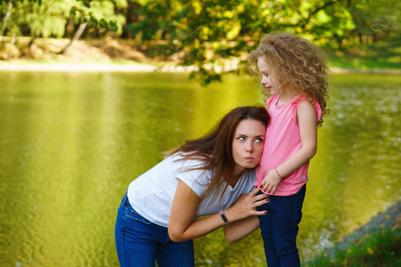 Family time. Mother and daughter play by the river. Woman put ear to little girl's belly Stock Photo