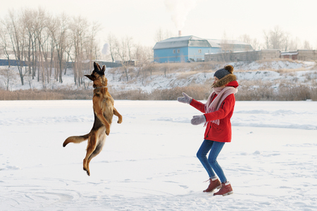 Teenager girl and German shepherd for a walk. Sunny winter day. Jumping dog catches a snowball.